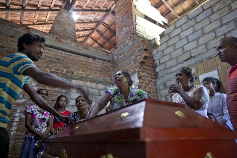 Lalitha, center, argues with a relative on weather to open the sealed-coffin to see her 12-year old niece, Sneha Savindi, who was a victim of Easter Sunday bombing at St. (AP Photo/Gemunu Amarasinghe)