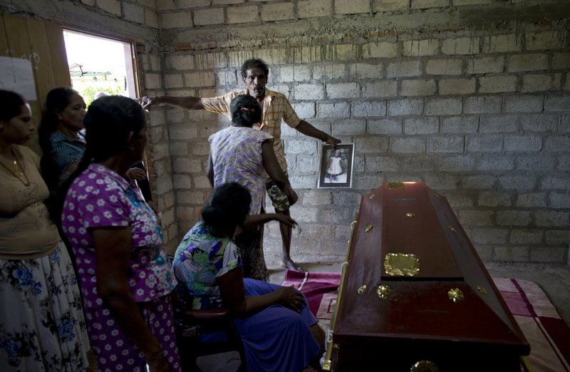 A relative holds an old portrait of 12-year Sneha Savindi, who was a victim of Easter Sunday bombing at St. (AP Photo/Gemunu Amarasinghe)
