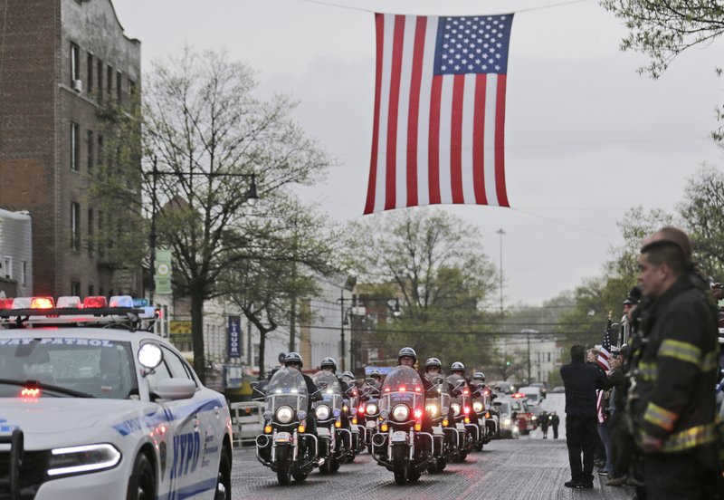 A procession escorting the body of Staff Sgt. Christopher Slutman arrives to a funeral home in the Bronx borough of New York, Monday, April 22, 2019. (AP Photo/Seth Wenig)