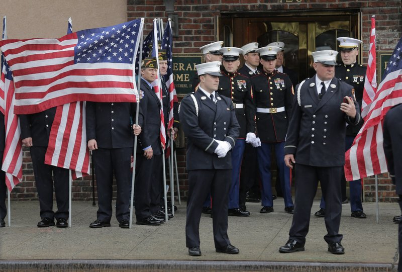 Service personnel prepare for the arrival of the body of Staff Sgt. Christopher Slutman in front of a funeral home in the Bronx borough of New York, Monday, April 22, 2019. (AP Photo/Seth Wenig)