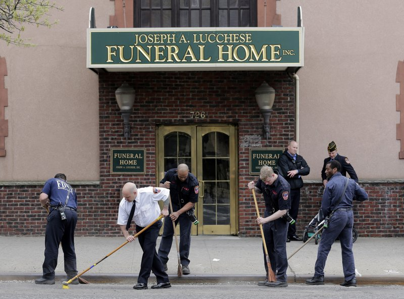 Firefighters sweep the street in front of a funeral home expecting the body of Staff Sgt. Christopher Slutman in the Bronx borough of New York, Monday, April 22, 2019. (AP Photo/Seth Wenig)