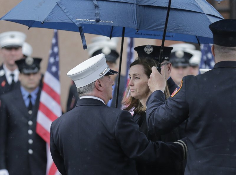 Shannon Slutman, wife of Staff Sgt. Christopher Slutman, watches as a casket containing her husband's body is moved into a funeral home in the Bronx borough of New York, Monday, April 22, 2019. (AP Photo/Seth Wenig)