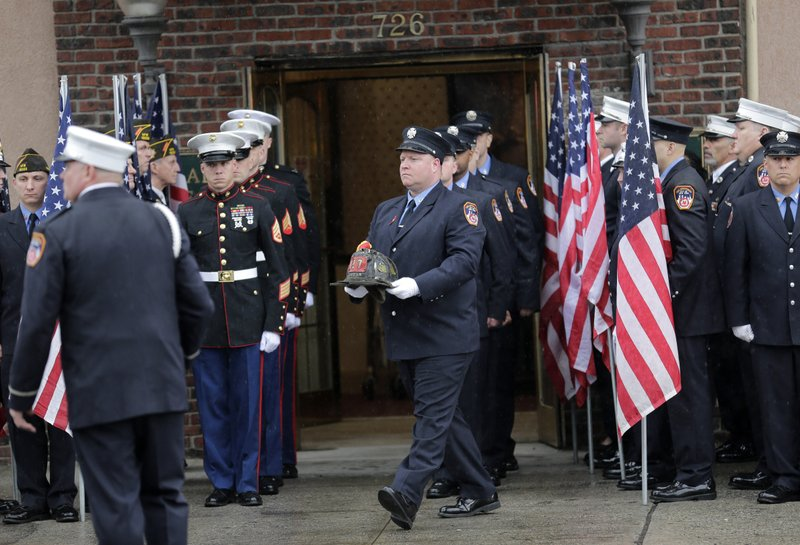 Firefighter, Marines and other service members prepare for the arrival of the body of Staff Sgt. Christopher Slutman to a funeral home in the Bronx borough of New York, Monday, April 22, 2019. (AP Photo/Seth Wenig)
