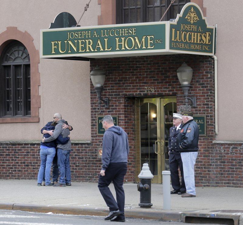 People embrace in front of a funeral home preparing to receive the remains of Staff Sgt. Christopher Slutman in the Bronx borough of New York, Monday, April 22, 2019. (AP Photo/Seth Wenig)