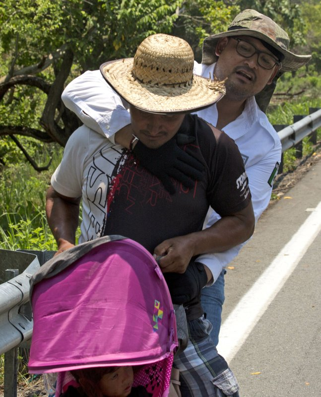 A Central American migrant pushing a child in a baby carriage is detained by a Mexican immigration agent on the highway to Pijijiapan, Mexico, Monday, April 22, 2019. (AP Photo/Moises Castillo)