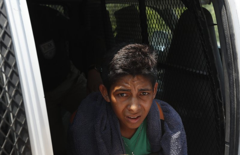 A Central American migrant detained by Mexican immigration agents looks out from a van on the highway to Pijijiapan, Mexico, Monday, April 22, 2019. (AP Photo/Moises Castillo)