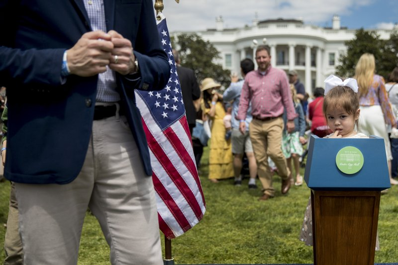 A girl stands at a little podium as her father stands nearby at the annual White House Easter Egg Roll on the South Lawn of the White House, Monday, April 22, 2019, in Washington. (AP Photo/Andrew Harnik)