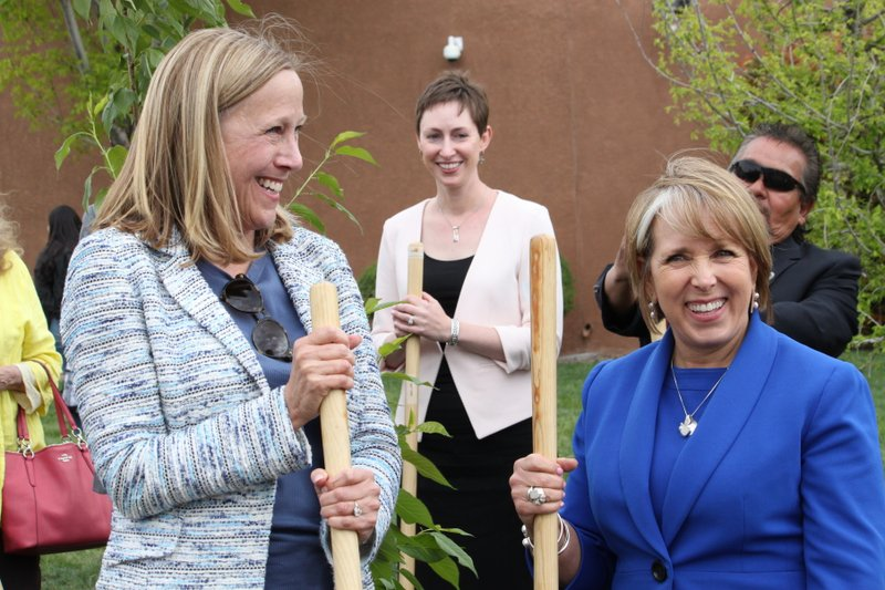 New Mexico Gov. Michelle Lujan Grisham, right, and PNM Resources CEO Pat Vincent-Collawn, left, celebrate after planting a tree for Earth Day in Albuquerque, N. (AP Photo/Susan Montoya Bryan)