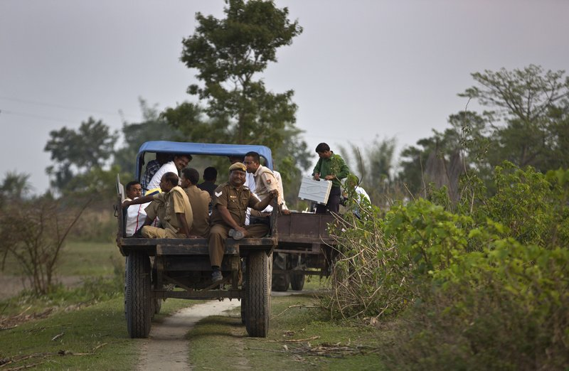 Indian election officials with polling materials board on a tractor after arriving at a river island in the River Brahmaputra in Kamrup district, west of Gauhati, Assam, India, Monday, April 22, 2019. (AP Photo/Anupam Nath)