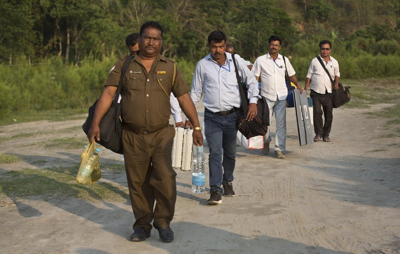Indian election officials with polling materials walk to board a country boat to reach a polling center in a remote river island in the River Brahmaputra in Kamrup district, west of Gauhati, Assam, India, Monday, April 22, 2019. (AP Photo/Anupam Nath)
