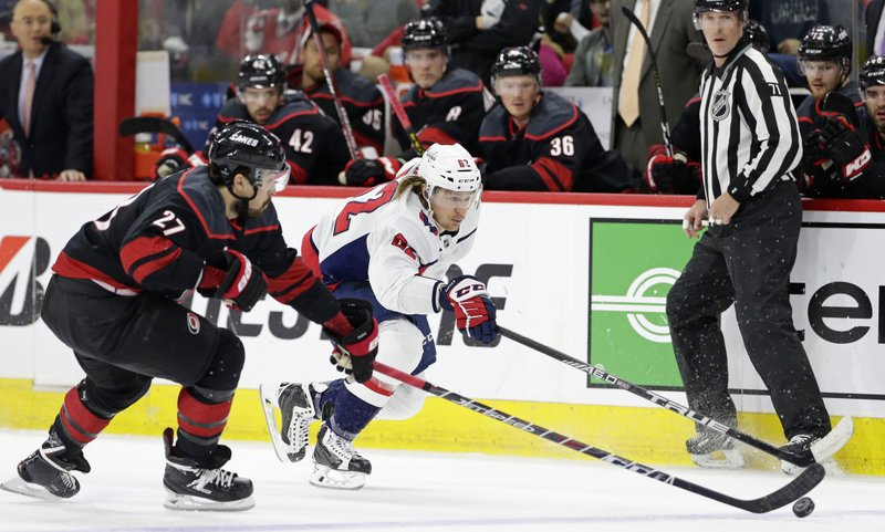 Carolina Hurricanes' Justin Faulk (27) and Washington Capitals' Carl Hagelin (62), of Sweden, chase the puck during the first period of Game 6 of an NHL hockey first-round playoff series in Raleigh, N. (AP Photo/Gerry Broome)