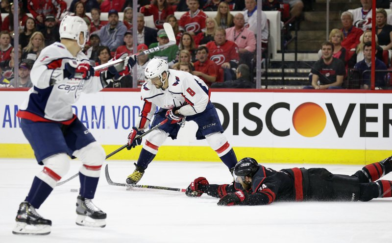 Carolina Hurricanes' Jaccob Slavin (74) falls to the ice while defending against Washington Capitals' Alex Ovechkin (8), of Russia, during the first period of Game 6 of an NHL hockey first-round playoff series in Raleigh, N. (AP Photo/Gerry Broome)