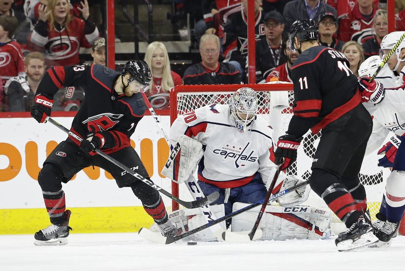 Carolina Hurricanes' Warren Foegele (13) tries to score against Washington Capitals goalie Braden Holtby (70) while Hurricanes' Jordan Staal (11) assists during the first period of Game 6 of an NHL hockey first-round playoff series in Raleigh, N. (AP Photo/Gerry Broome)