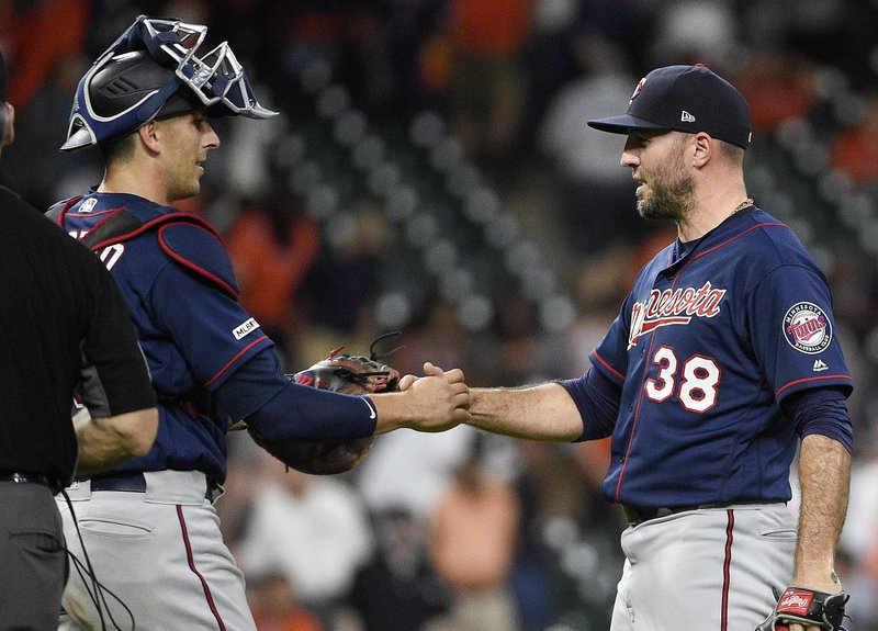 Minnesota Twins relief pitcher Blake Parker (38) shakes hands with catcher Jason Castro after their victory over the Houston Astros in a baseball game, Monday, April 22, 2019, in Houston. (AP Photo/Eric Christian Smith)