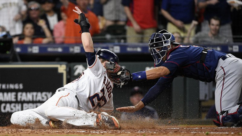 Houston Astros' Josh Reddick, left, is tagged out at home by Minnesota Twins catcher Jason Castro during the fourth inning of a baseball game, Monday, April 22, 2019, in Houston. (AP Photo/Eric Christian Smith)