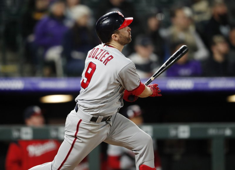 Washington Nationals' Brian Dozier follows the flight of his three-run home run off Colorado Rockies starting pitcher Tyler Anderson in the fourth inning of a baseball game Monday, April 22, 2019, in Denver. (AP Photo/David Zalubowski)