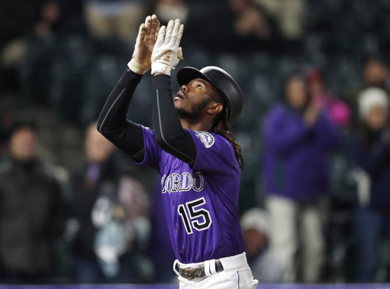Colorado Rockies pinch-hitter Raimel Tapia gestures as he crosses home plate after hitting a solo home run off Washington Nationals relief pitcher Kyle Barraclough in the eighth inning of a baseball game Monday, April 22, 2019, in Denver. (AP Photo/David Zalubowski)