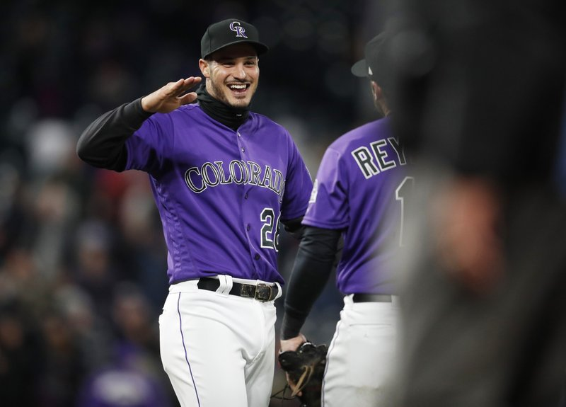 Colorado Rockies third baseman Nolan Arenado, left, celebrates with first baseman Mark Reynolds after Arenado turned a double play against the Washington Nationals to end the ninth inning of a baseball game, Monday, April 22, 2019, in Denver. (AP Photo/David Zalubowski)