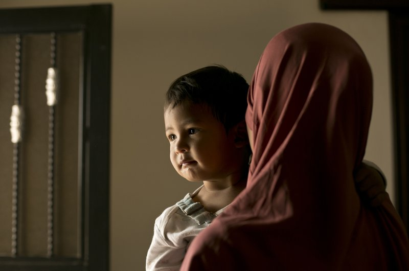 """In this March 26, 2019, photo, Aliya, a 24 year-old Indonesian national, poses for a portrait with her son, Yahya, at Camp Roj in north Syria. (migration to the caliphate), all your sins are cleared,"""" she said. (AP Photo/Maya Alleruzzo)"""