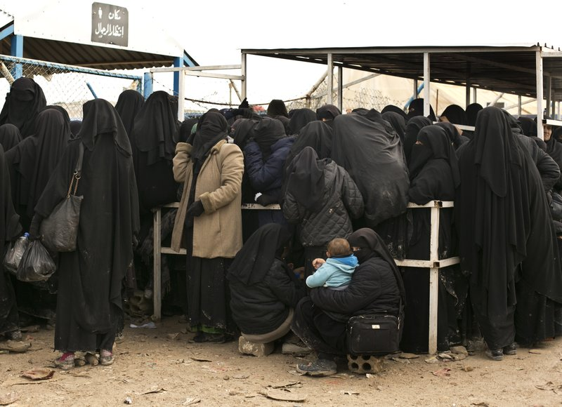 In this Sunday, March 31, 2019, photo, women line up for aid supplies at Al-Hol camp in Hassakeh province, Syria. (AP Photo/Maya Alleruzzo)