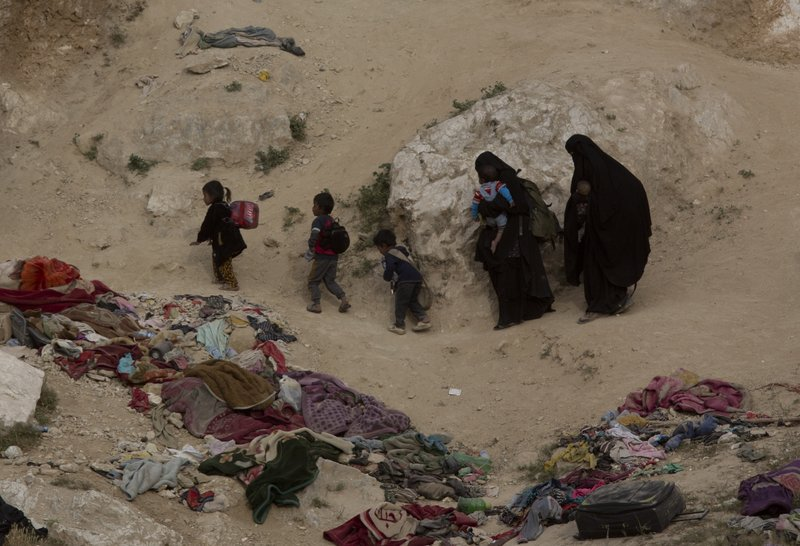 FILE - In this March 14, 2019, file photo, Women and their children who left the besieged Islamic State-held village of Baghouz, Syria, scramble over a rocky hillside to be checked by U. (AP Photo/Maya Alleruzzo, File)