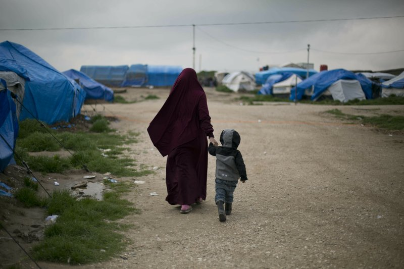 In this March 27, 2019, photo, Samira from Belgium walks with her son at Camp Roj in north Syria. She traveled to Syria, where Islamic State militants brought suitors for marriage. (AP Photo/Maya Alleruzzo)