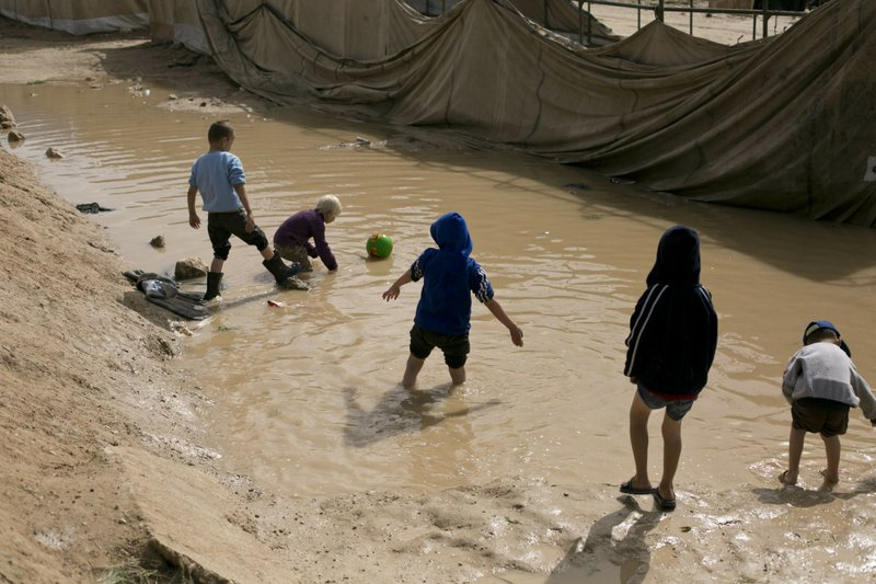 In this March 31, 2019, photo, children play in a mud puddle in the section for foreign families at Al-Hol camp in Hassakeh province, Syria. (AP Photo/Maya Alleruzzo)