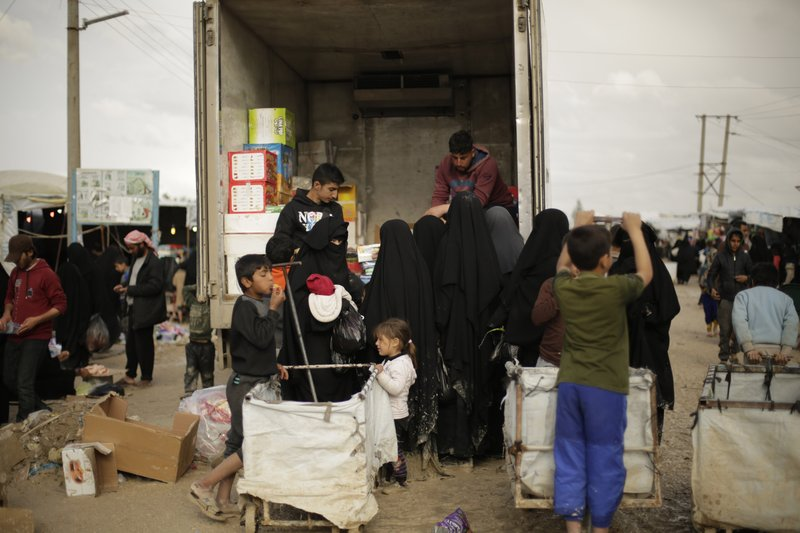 In this March 31, 2019, photo, women purchase goods from the back of a truck in the marketplace at Al-Hol camp, near Hassakeh, Syria. (AP Photo/Maya Alleruzzo)