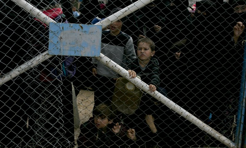 In this March 31, 2019 photo, children peer from the gate that closes off the section for foreign families who live in the Islamic State group's so-called caliphate, at Al-Hol camp in Hassakeh province, Syria. (AP Photo/Maya Alleruzzo)