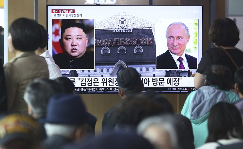 People watch a TV screen showing images of North Korean leader Kim Jong Un, left, and Russian President Vladimir Putin, right, during a news program at the Seoul Railway Station in Seoul, South Korea, Tuesday, April 23, 2019. (AP Photo/Ahn Young-joon)