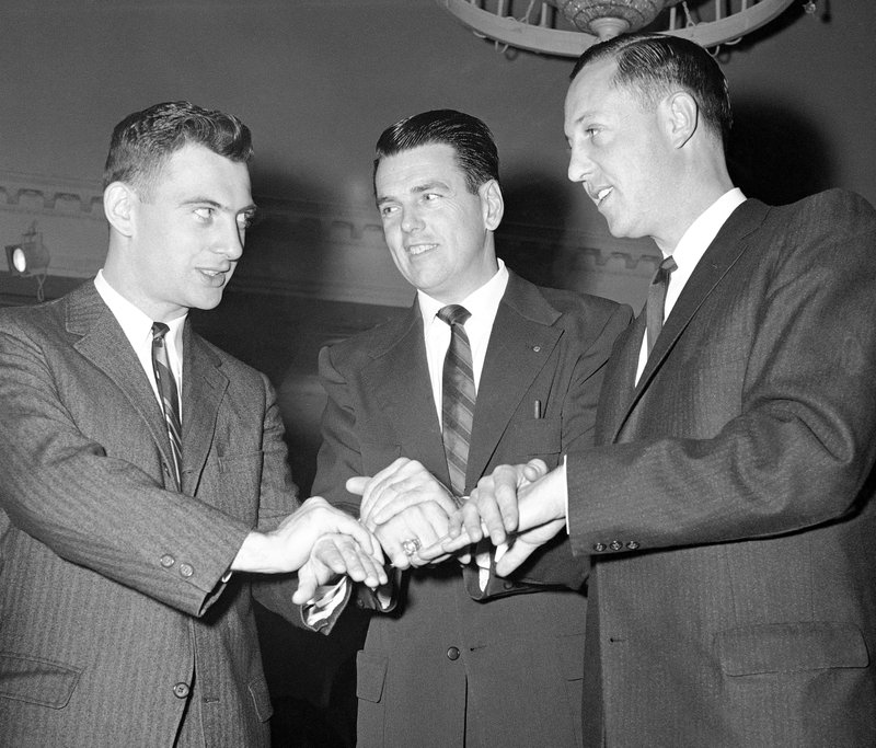 FILE - In this Dec. 1, 1958, file photo, from left, Dan Rooney, son of Pittsburgh Steelers owner Art Rooney, George Allen, assistant coach of the Chicago Bears and Pete Rozelle, general manager of the Los Angeles Rams, prepare to uncover coins determining picking order at the NFL Draft, in Philadelphia. (AP Photo/Sam Myers, File)