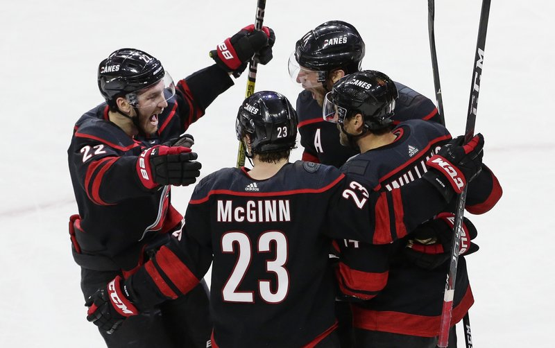 Carolina Hurricanes' Brett Pesce (22), Brock McGinn (23), Justin Williams, and Jordan Staal, top right, celebrate Williams' goal against the Washington Capitals during the third period of Game 6 of an NHL hockey first-round playoff series in Raleigh, N. (AP Photo/Gerry Broome)