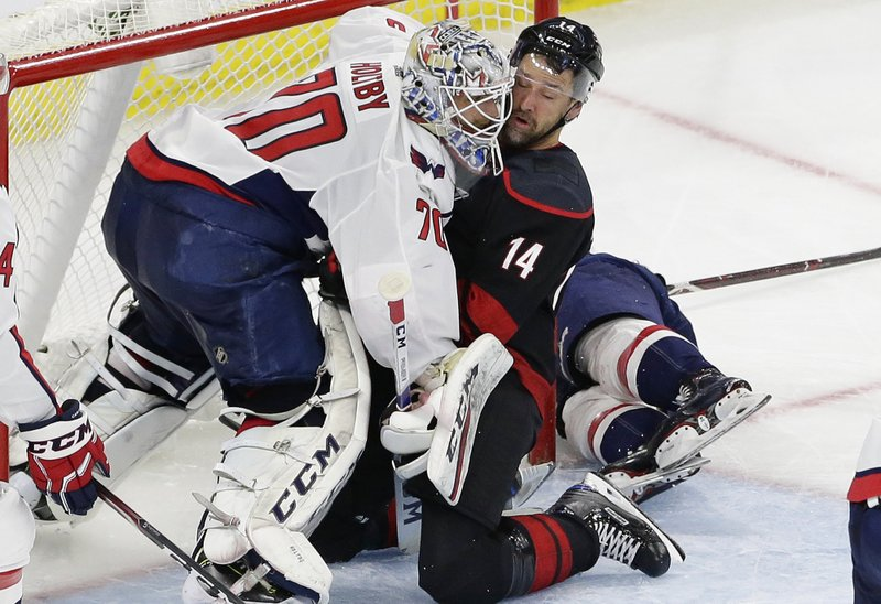 Carolina Hurricanes' Justin Williams (14) collides with Washington Capitals goalie Braden Holtby (70) during the second period of Game 6 of an NHL hockey first-round playoff series in Raleigh, N. (AP Photo/Gerry Broome)