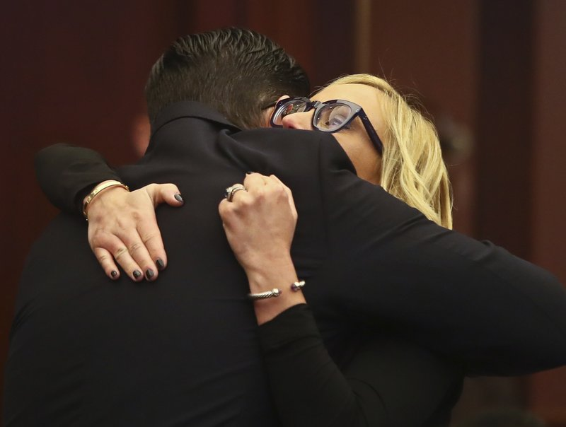 Sen. Manny Diaz, Jr., R-Hialeah, gets a hug from Sen. Lauren Book, D-Plantation, after his Senate Bill 7030: Implementation of Legislative Recommendations of the Marjory Stoneman Douglas High School Public Safety Commission passed 22-17 Tuesday, April 23, 2019, in the Florida Senate in Tallahassee, Fla. (AP Photo/Phil Sears)