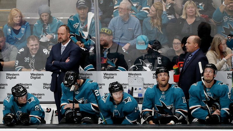 San Jose Sharks coach Peter DeBoer, left rear, stands in the bench area during the second period against the Vegas Golden Knights in Game 2 of an NHL hockey first-round playoff series Friday, April 12, 2019, in San Jose, Calif. (AP Photo/Josie Lepe)