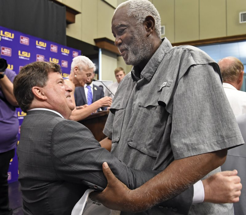 Former LSU basketball player Collis Temple Jr., right, greets Scott Woodward, left, after Woodward was introduced as the new Director of Athletics at LSU, Tuesday April 23, 2019, in Baton Rouge, La. (Bill Feig/The Advocate via AP)