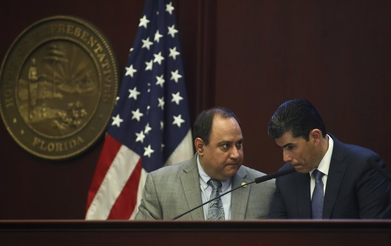Rep. Ray Rodrigues, R-Estero and House Speaker Jose Oliva, R- Miami Lakes, confer during debate over House Bill 7089 - Voting Rights Restoration, Tuesday April 23, 2019 in the Florida House of Representatives in Tallahassee, Fla. (AP Photo/Phil Sears)