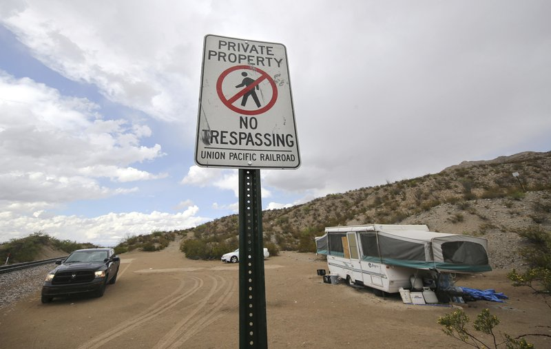 A Union Pacific Police unit sits guard as members of the United Constitutional Patriots group vacates their camp near the border in Anapra, N. (Mark Lambie/The El Paso Times via AP)