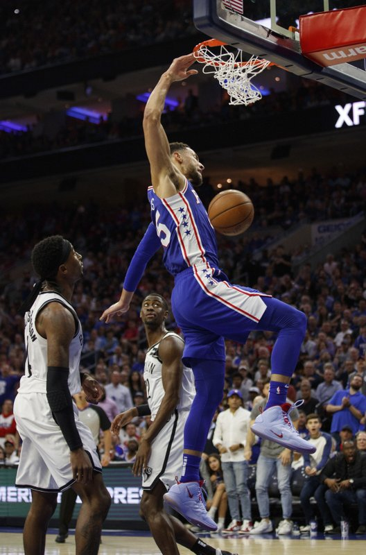 Philadelphia 76ers' Ben Simmons, right, of Australia, dunks the ball as Brooklyn Nets' Caris LeVert, center, and Rondae Hollis-Jefferson, left, watch during the first half in Game 5 of a first-round NBA basketball playoff series, Tuesday, April 23, 2019, in Philadelphia. (AP Photo/Chris Szagola)