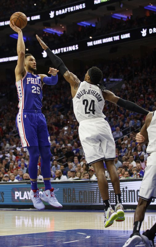 Philadelphia 76ers' Ben Simmons, left, of Australia, shoots the ball with Brooklyn Nets' Rondae Hollis-Jefferson, right, defending during the first half in Game 5 of a first-round NBA basketball playoff series, Tuesday, April 23, 2019, in Philadelphia. (AP Photo/Chris Szagola)