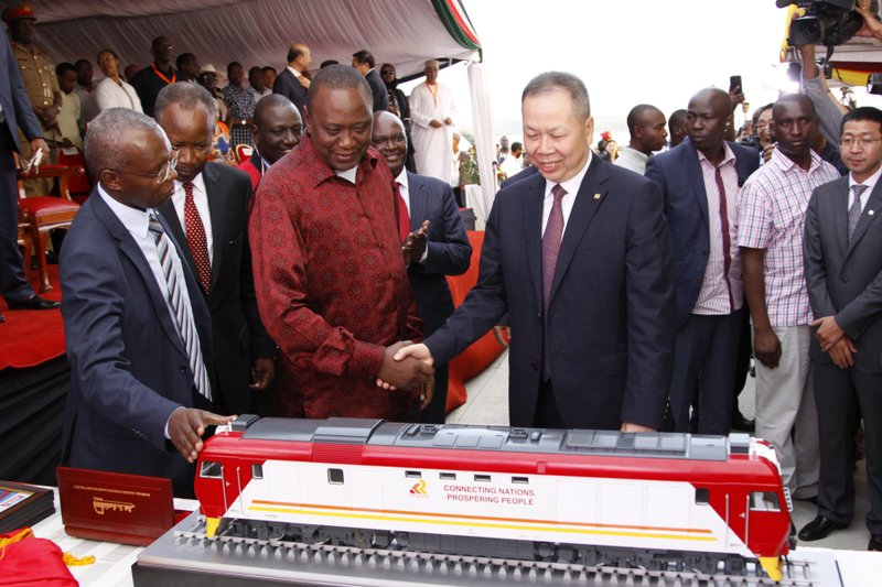 FILE - In this May 30, 2017, file photo, Kenyan President Uhuru Kenyatta, second from left, and Chen Fenjian, president of CCC, shakes hands next to a model of a locomotive during the opening of a Chinese-backed railway costing nearly $3. (AP Photo/Khalil Senosi, File)