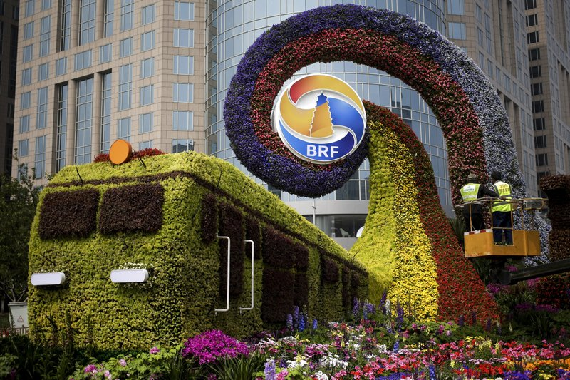 Workers on a platform install flowers on a decoration in a shape of a train for promoting the upcoming Belt and Road Forum in Beijing, Tuesday, April 23, 2019. (AP Photo/Andy Wong)