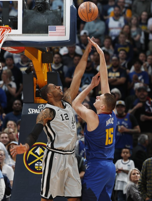 Denver Nuggets center Nikola Jokic (15) shoots over San Antonio Spurs center LaMarcus Aldridge (12) in the first half of Game 5 of an NBA basketball first round playoff series, Tuesday, April 23, 2019, in Denver. (AP Photo/David Zalubowski)