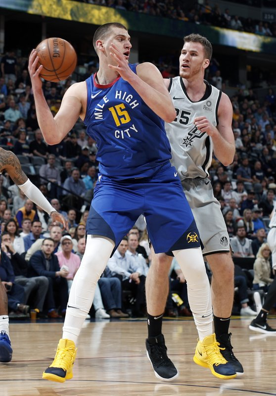Denver Nuggets center Nikola Jokic (15) is pressured by San Antonio Spurs center Jakob Poeltl (25) in the first half of Game 5 of an NBA basketball first-round playoff series Tuesday, April 23, 2019, in Denver. (AP Photo/David Zalubowski)