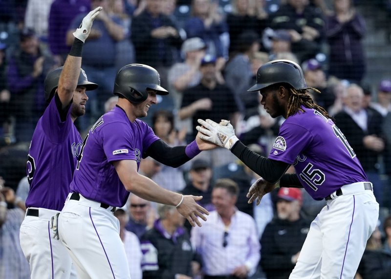Colorado Rockies' Raimel Tapia (15) is congratulated by teammate Ryan McMahon (24) after hitting a two run home run against the Washington Nationals during the second inning of a baseball game Tuesday, April 23, 2019, in Denver. (AP Photo/Jack Dempsey)