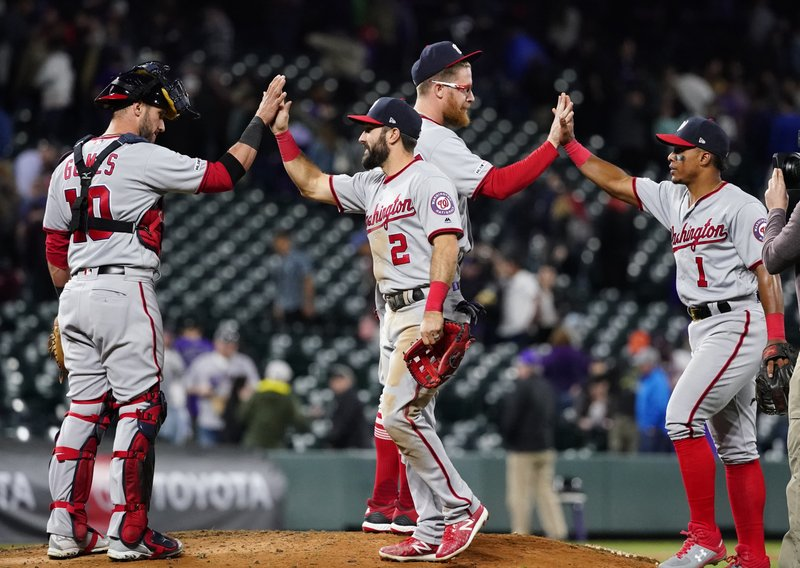 Washington Nationals right fielder Adam Eaton (2) and Wilmer Difo celebrate a 6-3 win against the Colorado Rockies with teammates Yan Gomes (10) and Sean Doolittle (63) after a baseball game, Tuesday, April 23, 2019, in Denver. (AP Photo/Jack Dempsey)
