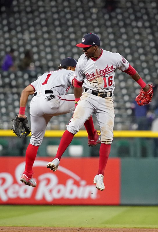 Washington Nationals center fielder Victor Robles (16) and Wilmer Difo celebrate a 6-3 win against the Colorado Rockies following a baseball game, Tuesday, April 23, 2019, in Denver. (AP Photo/Jack Dempsey)