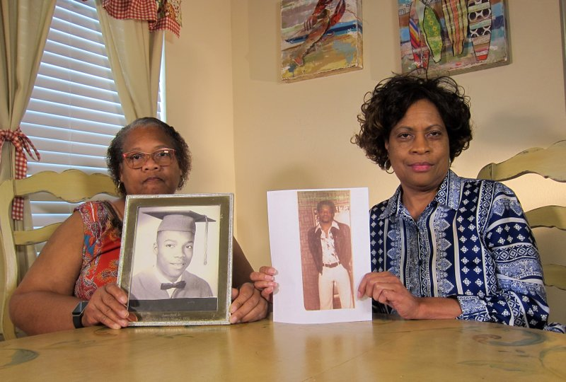 In this Wednesday, April 10, 2019, photo Mylinda Byrd Washington, 66, left, and Louvon Byrd Harris, 61, hold up photographs of their brother James Byrd Jr. (AP Photo/Juan Lozano)