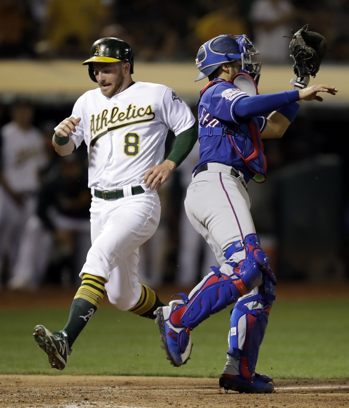 Oakland Athletics' Robbie Grossman (8) scores behind Texas Rangers catcher Isiah Kiner-Falefa, right, in the fourth inning of a baseball game, Tuesday, April 23, 2019, in Oakland, Calif. (AP Photo/Ben Margot)