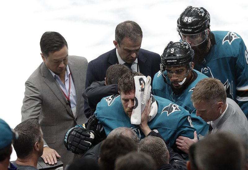 San Jose Sharks center Joe Pavelski, bottom center, is helped off the ice during the third period of Game 7 of an NHL hockey first-round playoff series against the Vegas Golden Knights in San Jose, Calif. (AP Photo/Jeff Chiu)